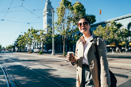 beautiful chinese female traveler smiling holding coffee cup walking crossing the railway of cable car streetcar outdoors in san francisco after sightseeing the famous attraction ferry building usa