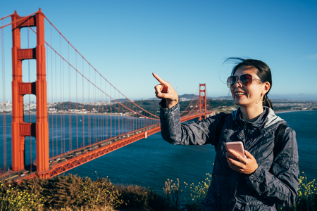 Golden gate Bridge happy hiking young lady tourist sightseeing in San Francisco USA. girl tourist excited pointing at blue sky holding mobile searching the direction online map in California US. Stock Photo