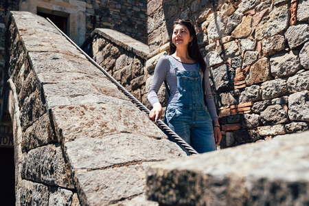 Decaying staircase in an abandoned historic old medieval castle. young asian girl tourist in overalls walking down stone stairs visiting ancient palace outdoors on sunny day holding the rope. Stock Photo