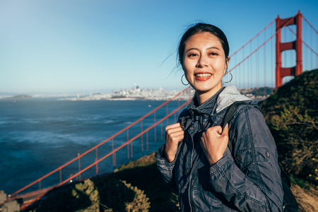 cheerful woman tourist laughing by Golden Gate Bridge in san francisco. beautiful girl backpacker standing on mountain hills face camera smiling under sunshine. blue clean sky and sea ocean water. Banque d'images
