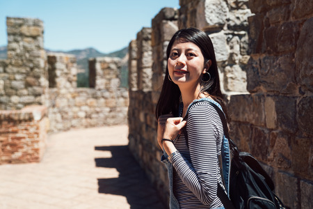 beautiful girl backpacker walking on the roof of the historical castle in europe. young asian woman face camera smiling attractive under sunny day in summer vacation self guided travel trip. Stock fotó