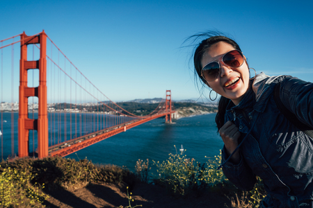 Happy young female tourists wearing sunglasses taking selfie in San Francisco by Golden Gate Bridge USA. asian woman face camera smiling attractive taking self portrait with famous attraction in us. Фото со стока