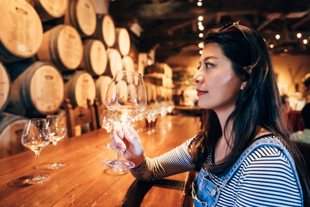 Happy young asian lady tasting wine sitting in the restaurant in napa valley alone. elegant female professional wine steward working doing her job in the grapery bar indoor. room underground cellar