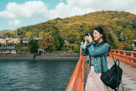 asian lady tourist taking photo on wooden bridge above uji river in kyoto japan. young woman backpacker shooting by professional slr camera visiting tour trip in spring. green mountain in back.