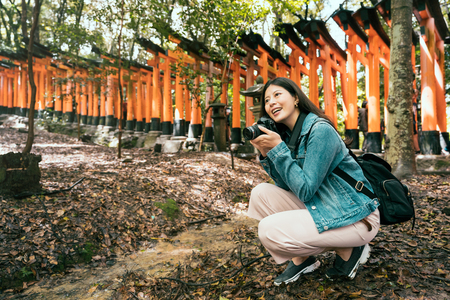 beautiful asian backpacker kneeling down in nature forest in japanese temple holding professional camera taking picture. young girl photographer in inari shrine kyoto japan joyfully smiling. Stockfoto