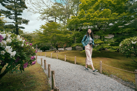 full length of young girl tourist walking in japanese garden on little path with stone road. colorful flowers green trees grass surrounding passway in kyoto japan in spring. female lady relax enjoy