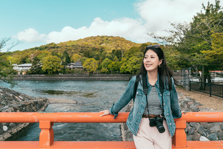 female tourist relying on red wooden handrail above the uji lake canal on bridge Japan. green mountain and trees beautiful nature in background. young girl enjoy sun smiling.