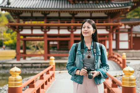 Traveling young photographer outdoors walking on bridge in uji kyoto japan. asian girl tourist relaxing happy sightseeing around in japanese temple with good weather. female traveler holding camera. 版權商用圖片