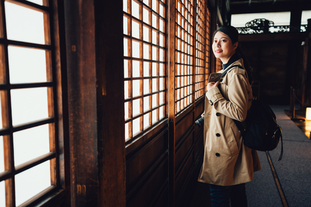 young girl traveler photographer with camera standing in corridor near paper sliding doors called Shoji in Japanese. asian lady visit japan monument nijo jo fitland castle indoors. woman carry bag.