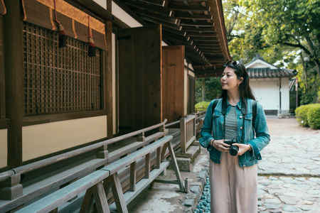 asian woman backpacker photographer sightseeing visiting in ujigami jinja in spring in kyoto japan. girl in sunglasses holding camera looking into window of wooden building house japanese style.