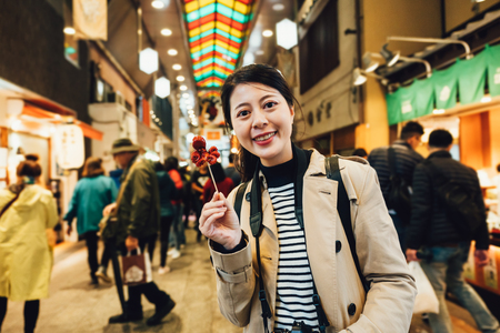 woman tourist photographer cheerful holding stick with little octopus on it showing camera. happy young girl traveler trying japanese snack street food nishiki ichiba. people shopping brocade market 版權商用圖片