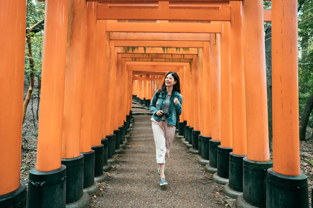 full length of young asian woman traveler walking in torii cheerfully smiling. female photographer holding professional camera sightseeing in inari shrine kyoto japan. lady backpacker happy jump run.
