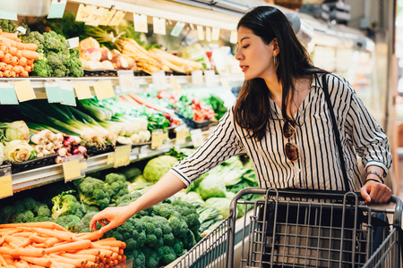 Japonka w supermarkecie popychając koszyk chodzący przez obszar warzyw i owoców. ładna azjatycka pani zbierając marchewki obok brokułów zakup żywności opieki zdrowotnej. żona przygotowuje się do obiadu Zdjęcie Seryjne