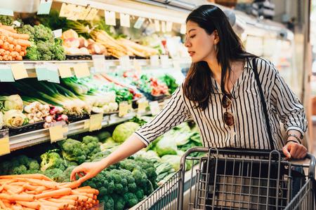 Mujer japonesa en el supermercado empujando el carrito de compras caminando por la zona de frutas y verduras. Señora bonita asiática recogiendo zanahorias al lado de brócoli compra alimentos sanitarios. esposa prepararse para la cena Foto de archivo