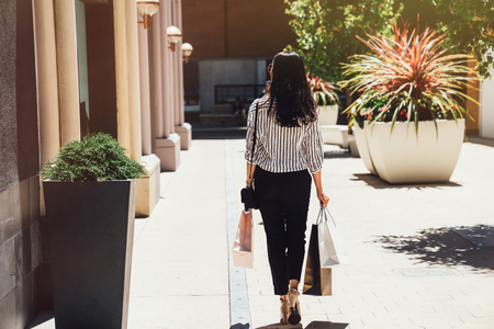 back view of young beautiful girl walking holding shopping bags on sunny day outdoors. asian lady in smart casual buying in christmas sale on boxing day. woman with black long hair in center mall. Stock Photo