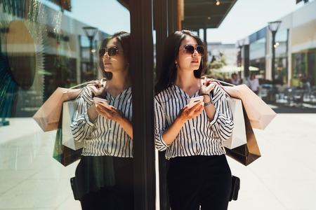 Fashion girl in sunglasses standing outdoor holding cellphone searching right direction cloth shop online map app on internet. young asian lady carrying shopping bag in stnford shopping mall center