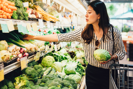 asian local woman buy vegetables and fruits in supermarket. young chinese lady holding green leaf vegetable and picking choosing green onion on cold open refrigerator. elegant female grocery shopping Standard-Bild