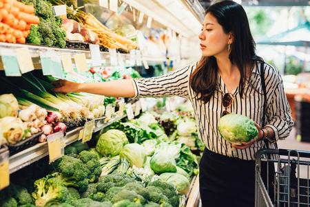 asiatische einheimische Frau kauft Gemüse und Obst im Supermarkt. junge chinesische dame, die grünes blattgemüse hält und grüne zwiebeln auf kaltem offenem kühlschrank wählt. elegante weibliche Lebensmitteleinkäufe Standard-Bild