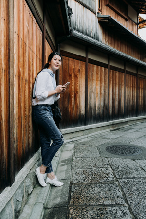 young japanese girl holding mobile phone relying on wooden wall waiting for friend. smiling asian woman using cellphone texting message chatting online. beautiful lady relaxing path way ishibe alley