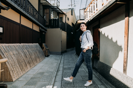 full length of young asian girl travel backpacker standing on road in Ishibe alley kyoto japan. female tourist traveling alone walking on street. beautiful woman sightseeing city attraction Zdjęcie Seryjne - 115663051
