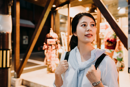asian woman backpacker standing in dark street in front of kimono shop in Hanamikoji Dori street at night. young female tourists love renting traditional kimono dress cloth in kyoto japan. 写真素材