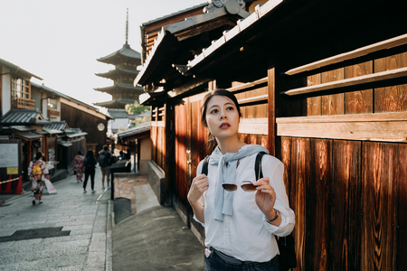female traveler holding sunglasses looking around in sannen zaka street. Yasaka Pagoda japanese style building in background famous attraction kyoto japan. people wearing kimono walking on the road. Stock Photo