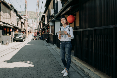 full length of young girl backpacker visiting Hanamikoji street standing on road holding paper map. japanese wooden building house hanging bamboo curtain on roof. woman finding direction destination.