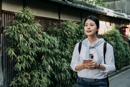 Female asian tourist using information from travel blogs browsed on mobile phone pass bamboo garden of japanese wooden house kyoto japan. girl navigating via application on smartphone walk outdoors