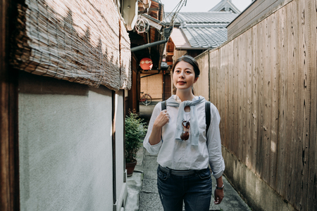 Girl backpacker walking through the typical narrow streets of ishibe alley kyoto japan. young asian woman in sunglasses cheerful relaxing in little path with bamboo curtain hanging on wooden house. Banco de Imagens
