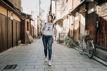 full length of young girl travel backpacker walking on road in ishibe alley kyoto japan. japanese old history town hosue made of wooden and bamboo. bike stop in street near the mail box. Zdjęcie Seryjne - 115661189