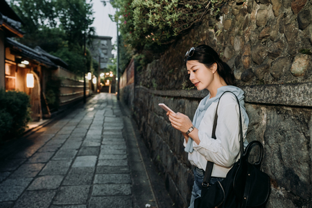 local japanese lady waiting along the stone wall standing on quiet passageway. woman backpacker holding cellphone smiling chatting online carrying backpack ready for date in night kyoto japan. Stock Photo
