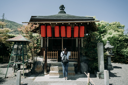 full length back view of beautiful asian girl backpacker praying at the shrine in kyoto japan. red lanterns hanging on roof of peaceful temple under sunny day blue sky green mountain. toro stone lamp