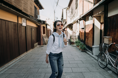 happy female backpacker in sunglasses visiting famous history old town in kyoto japan walking on stone road in ishibe alley kyoto. cheerful young lady tourist wearing casual suit sightseeing.