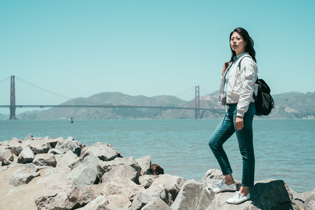 full length of young girl backpacker standing on stone rocks near the sea on the bay sightseeing under sunshine in summer america. red golden state bridge in background with nature amazing mountain. Stock Photo