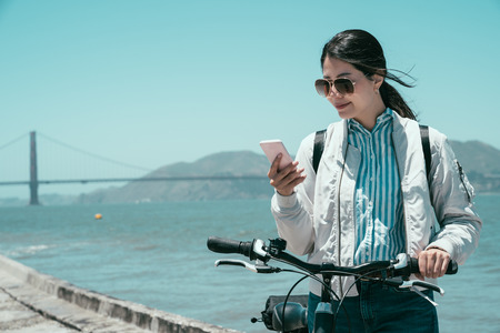 girl traveler walk with bike in summer travel in san francisco usa. golden gate bridge in background with mountain under blue sky. asian woman smiling using mobile phone searching online information.