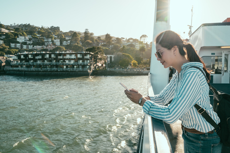 asian woman relaxing on balcony enjoying nature landscape view. girl backpacker sunglasses tourist holding cellphone standing on ferry boat going to marin county. lady searching information of sausalito Stock Photo