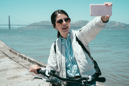 Happy young female tourist taking selfie in San Francisco by Golden Gate Bridge USA by smartphone. girl traveler in sunglasses with bike using mobile phone take self portrait under sunshine. Stock Photo