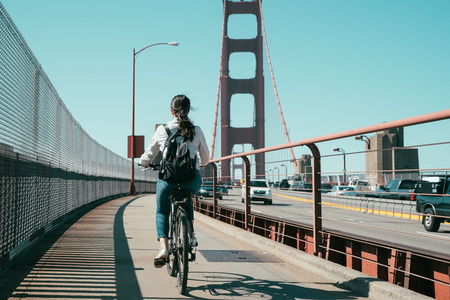 Bicyclist riding bike on pedestrian path of the Golden Gate Bridge california usa. back view of young asian lady cycling with cars traffic drive through pass. female backpacker sitting on bicycle.