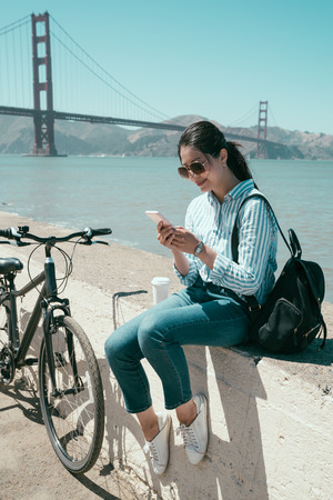 asian female college student looking in mobile phone touching screen and pausing on bay along the coast by riding bike. young happy girl texting message on cellphone sitting relaxing under sunlight. 写真素材