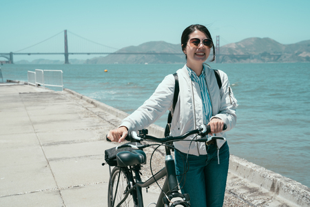 asian tourist woman in sunglasses using bicycle as means of transportation self guided tour trip in san francisco america in summer. young girl walk with bike near the ocean bay with golden bridge. Imagens