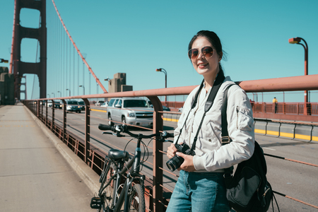 travel backpacker photographer relaxing standing by bike on pathway beside the road on golden gate bridge holding camera sightseeing beautiful nature view from high point to city urban san francisco