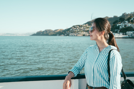 girl backpacker with sunglasses smiling enjoy sightseeing beautiful ocean on boat. Luxury travel holiday woman relaxing on balcony looking at view of mountains and nature landscape to marin county.