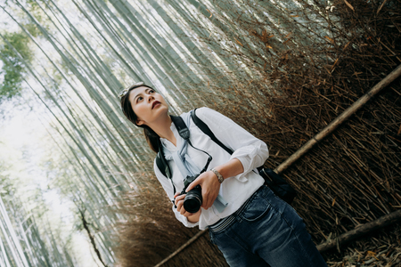 Woman photographer taking photo in the forest with backpack and travel lifestyle relaxation enjoy on autumn and summer weekend kyoto japan. young girl in sunglass look up beautiful blue sky Stockfoto