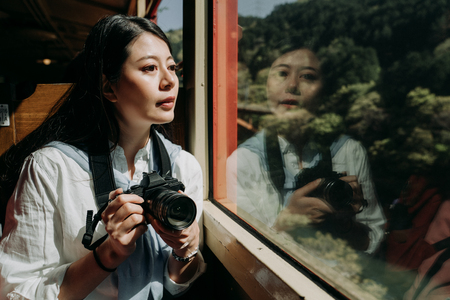 Girl tourist is looking out the window while sitting in fast train seat. young female backpacker photographer holding camera sightseeing beautiful nature view in spring. professional photographer travel.