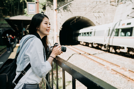 Young Asian woman photographer holding professional slr camera with confident smile taking picture of fast train in kyoto japan. girl backpacker cheerful standing outdoor near the railway cave.