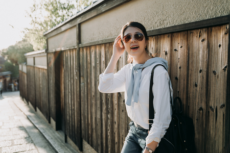 local japanese woman tour guide relying on wooden wall waiting for tourists finish visit old historical town. young girl in sunglasses working carrying backpack relaxing enjoy sunshine on weekend. Stock Photo