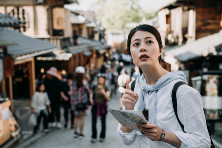 asian woman tourist holding paper map pointing to direction standing in Sannen Zaka street kyoto japan. girl backpacker self guided trip in summer vacation travelers visit famous attraction old town.