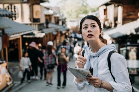Aziatische vrouw toerist met papieren kaart wijzend naar richting staande in Sannen Zaka street kyoto japan. meisje backpacker zelfgeleide reis in de zomervakantie reizigers bezoeken de beroemde attractie oude stad.