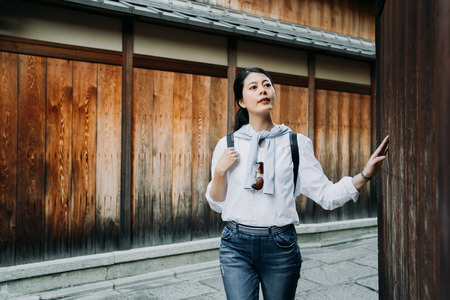 young girl backpacker hands touching wooden wall curiously sightseeing old town with teeming festival. female tourist standing on street of ishibe alley kyoto japan self guide trip.