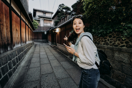 young travel female backpacker cheerful holding cellphone online map finding destination pointing finger standing in Ishibe alley. girl tourist face camera smiling finding hotel in kyoto japan. Banque d'images